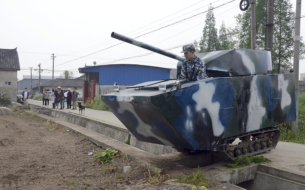 Jian drives his home-made replica of a tank past a small bridge above a ditch during a trial run, at a village in Mianzhu, Sichuan province