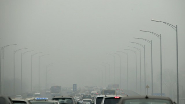 Cars travel on an overpass amid thick haze in the morning in Beijing